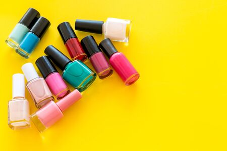 Choose nail polish. Polish bottels on yellow background top view copy space Stok Fotoğraf