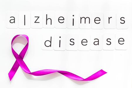 Alzheimers disease text near violet ribbon on white background top view