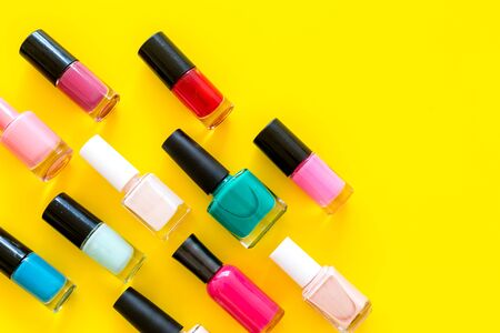 Nail polishes background on yellow table top view pattern copy space