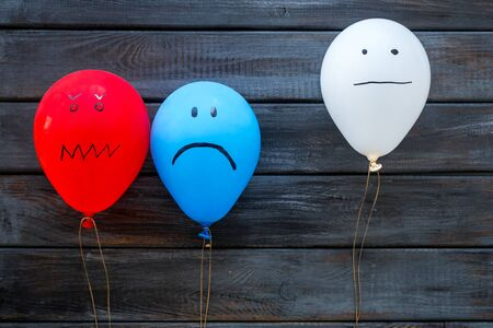 Negative emotions concept. Balloons with drawn faces on dark wooden background top view Reklamní fotografie
