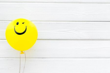 Happiness emotion. Yellow balloon with smile on white wooden background top view copy space Imagens
