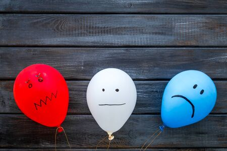 Negative emotions concept. Balloons with drawn faces on dark wooden background top view copy space