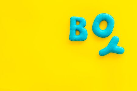 Boy word as decoration for baby shower on yellow background top view frame copy space Stock Photo