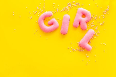 Girl word as decoration for baby shower on yellow background top view copy space 版權商用圖片