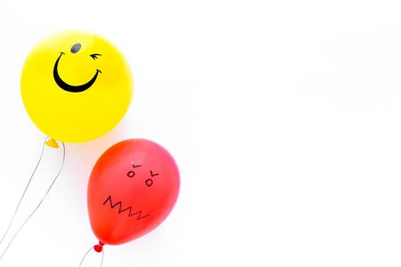 Treat depression concept. Balloons with frustrated and smiling faces on white background top view copy space