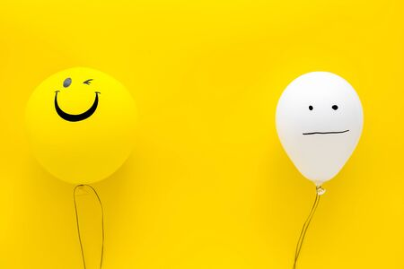 Treat depression concept. Balloons with frustrated and smiling faces on yellow background top view copy space