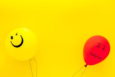 Treat depression concept. Balloons with frustrated and smiling faces on yellow background top view space for text Reklamní fotografie