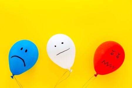 Negative emotions concept. Balloons with drawn faces on yellow background top view space for text