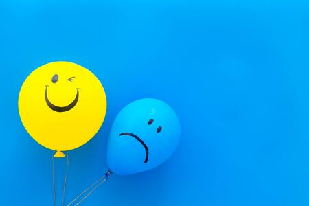 Treat depression concept. Balloons with sad and smiling faces on blue background top view copy space Reklamní fotografie
