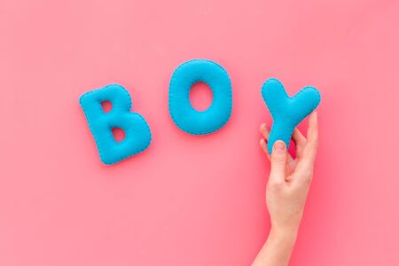Boy word as decoration for baby shower on pink background top view Stock Photo
