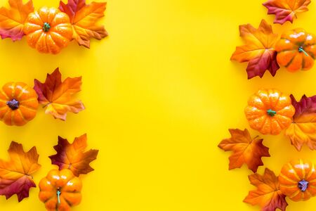 Autumn frame with colorful leaves and pumpkins on yellow background top view space for text