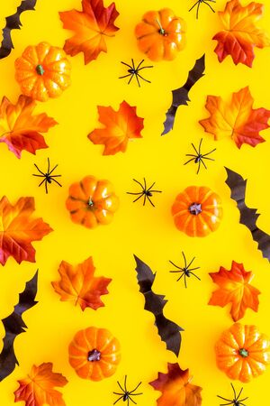 Halloween pattern with pumpkins, spiders and bats on yellow background top view
