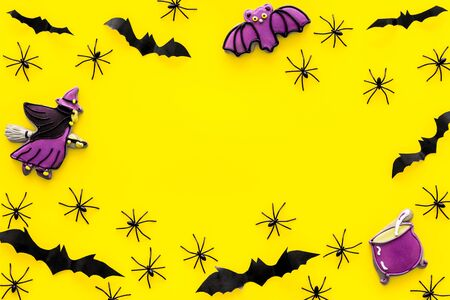 Cute Halloween decoration. Bats, spiders and special cookies on yellow background top view space for text