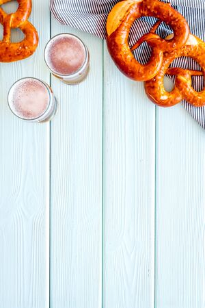 Octoberfest table background. Pretzels and beer glasses on blue wooden background top view frame space for text