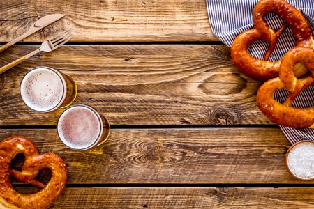 Octoberfest table background. Pretzels and beer glasses on dark wooden background top view frame space for text Stock Photo