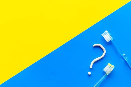 Dental problems. Question mark drawn with toothpaste near toothbrush on yellow and blue background top view copy space