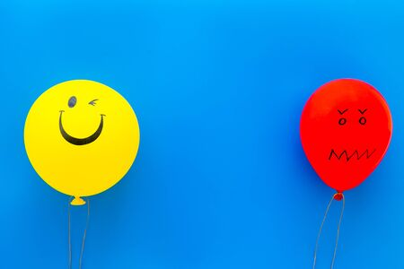 Treat depression concept. Balloons with frustrated and smiling faces on blue background top view copy space
