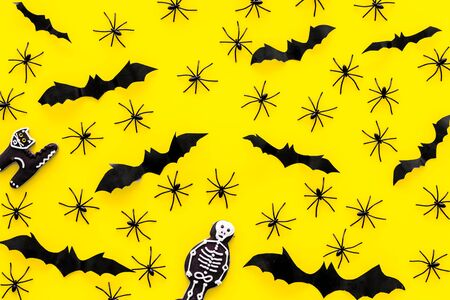 Cute Halloween decoration. Bats, spiders and special cookies on yellow background top view pattern