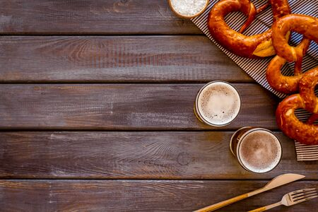 Octoberfest table background. Pretzels and beer glasses on dark wooden background top view frame copy space