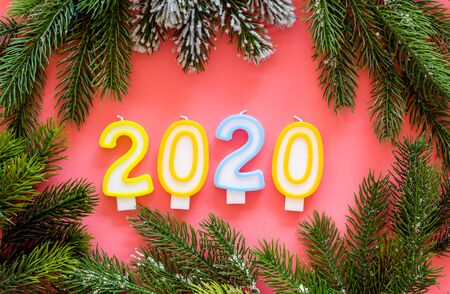 2020 New Year design. Date laid out by candles near fir branches on pink background top view.
