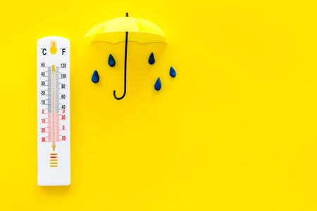 Rain concept. Weather thermometer near umbrella and drops on yellow background top view.