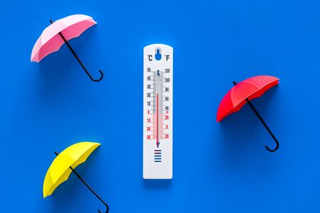 Rain concept. Weather thermometer near drops on blue background top view. Stockfoto