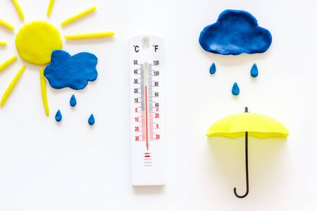 Rain concept. Weather thermometer near umbrella and drops on white background top view.