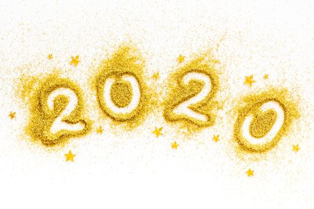 2020 Happy New Year. Date written on golden dust on white background top view.