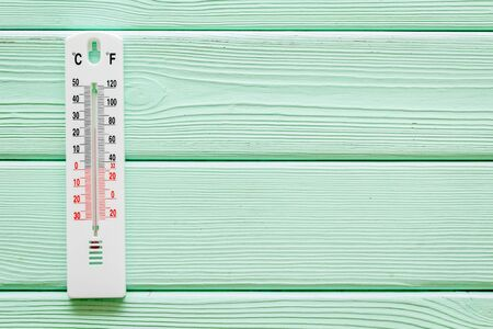 Weather thermometer on green wooden background top view. 스톡 콘텐츠