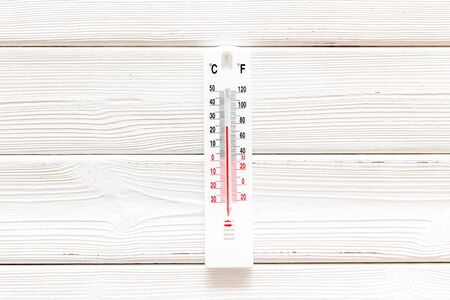 Weather thermometer on white woode background top view. Stock Photo