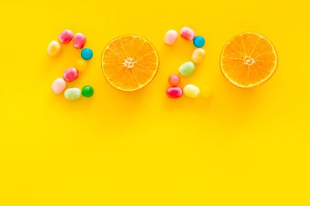 Sweet New Year design. 2020 laid out with candy and oranges on yellow background top view.