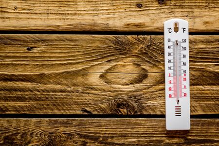 Weather thermometer on dark wooden background top view.