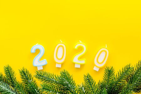 2020 New Year design. Date laid out by candles near fir branches on yellow background top view.