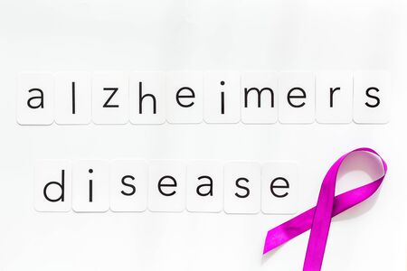 Alzheimers disease text near violet ribbon on white background top view.