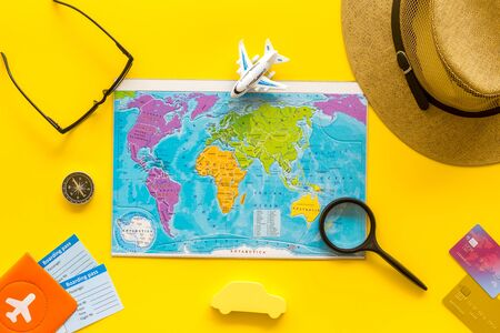 Planning a travel concept. Map of the world and tourist accessories on yellow background top view.