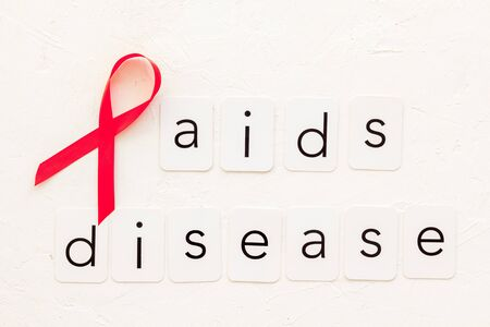 AIDS disease text near red ribbon on white background top view. Reklamní fotografie