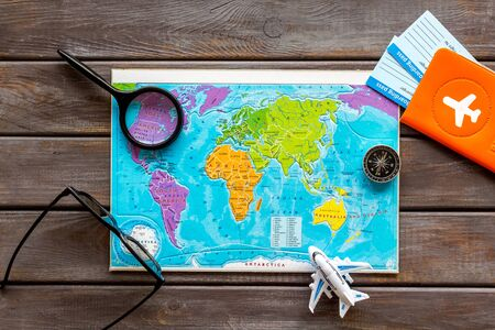 Planning a travel concept. Map of the world and tourist accessories on dark wooden background top view.
