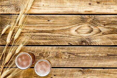 Barley or wheat as beer ingredient near beer glasses on rustic wooden background top view copy space