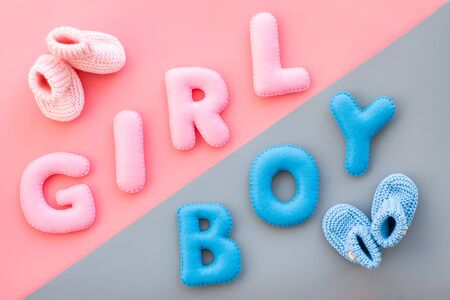Baby shower concept. Words boy and girl near booties on pink and blue background top view