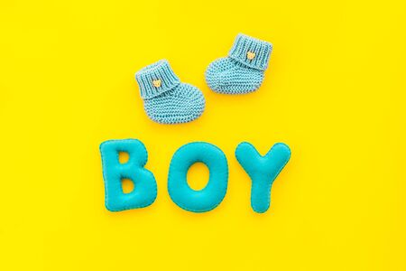Childrens birthday concept. Word boy near booties on yellow background top view