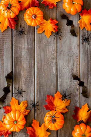 Halloween pattern with pumpkins, spiders and bats on dark wooden background top view copy space