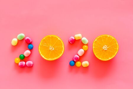 Sweet New Year design. 2020 laid out with candy and oranges on pink background top view copy space