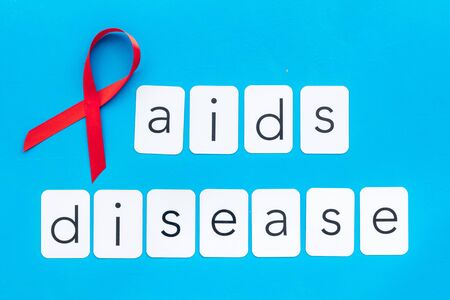 AIDS disease text near red ribbon on blue background top view 版權商用圖片