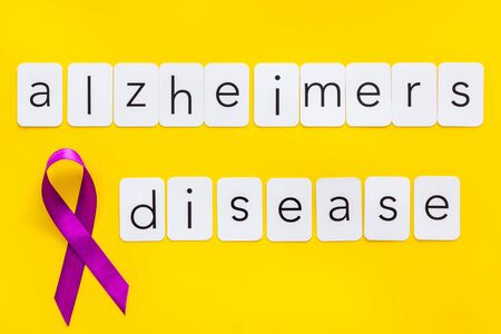 Alzheimers disease text near violet ribbon on yellow background top view Zdjęcie Seryjne