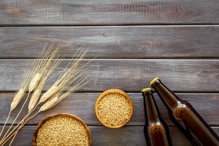 Beer ingredients. Barley near beer bottles on dark wooden background top view copy space Stock Photo