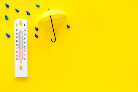 Rain concept. Weather thermometer near umbrella and drops on yellow background top view copy space