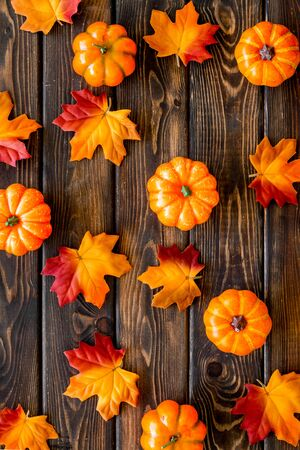 Autumn composition. Pattern with red and orange leaves and pumpkins on dark wooden background top view