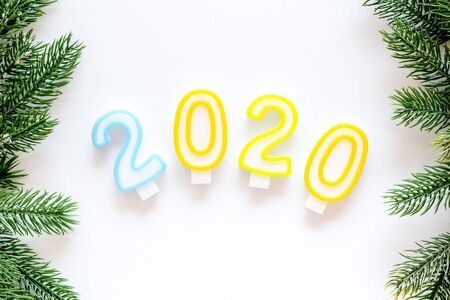 2020 New Year design. Date laid out by candles near fir branches on white background top view copy space