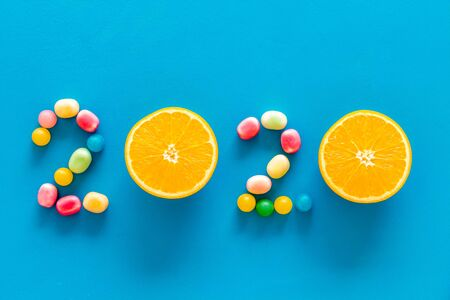 Sweet New Year design. 2020 laid out with candy and oranges on blue background top view