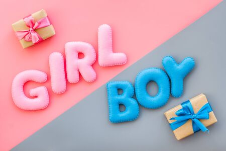 Baby shower concept. Words boy and girl near present box on pink and blue background top view